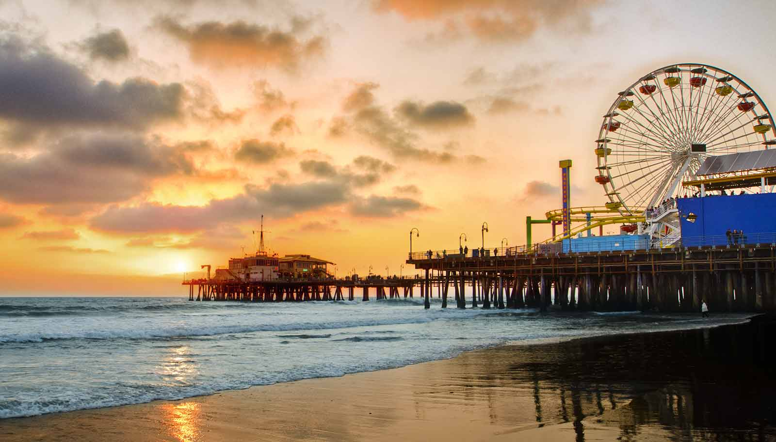 sunset of Santa Monica pier with ferris wheel and ocean waves